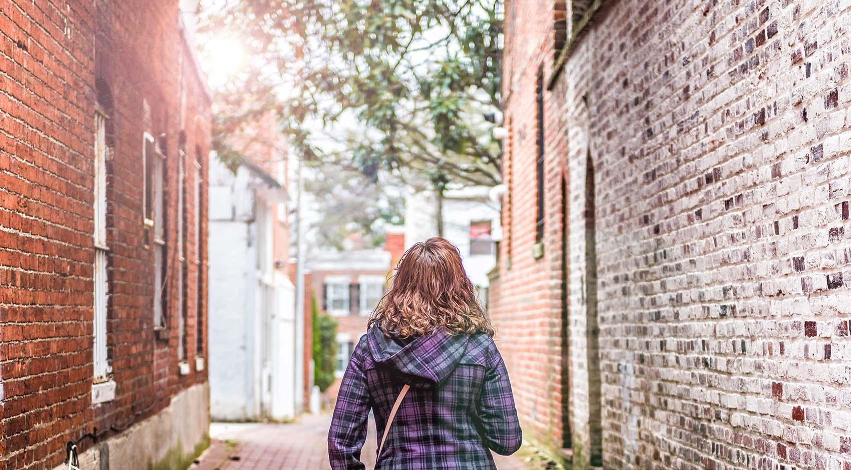 Woman walking through brick alley way